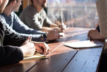 Des hommes assis à une table dans un bureau, lors d'une réunion de travail.