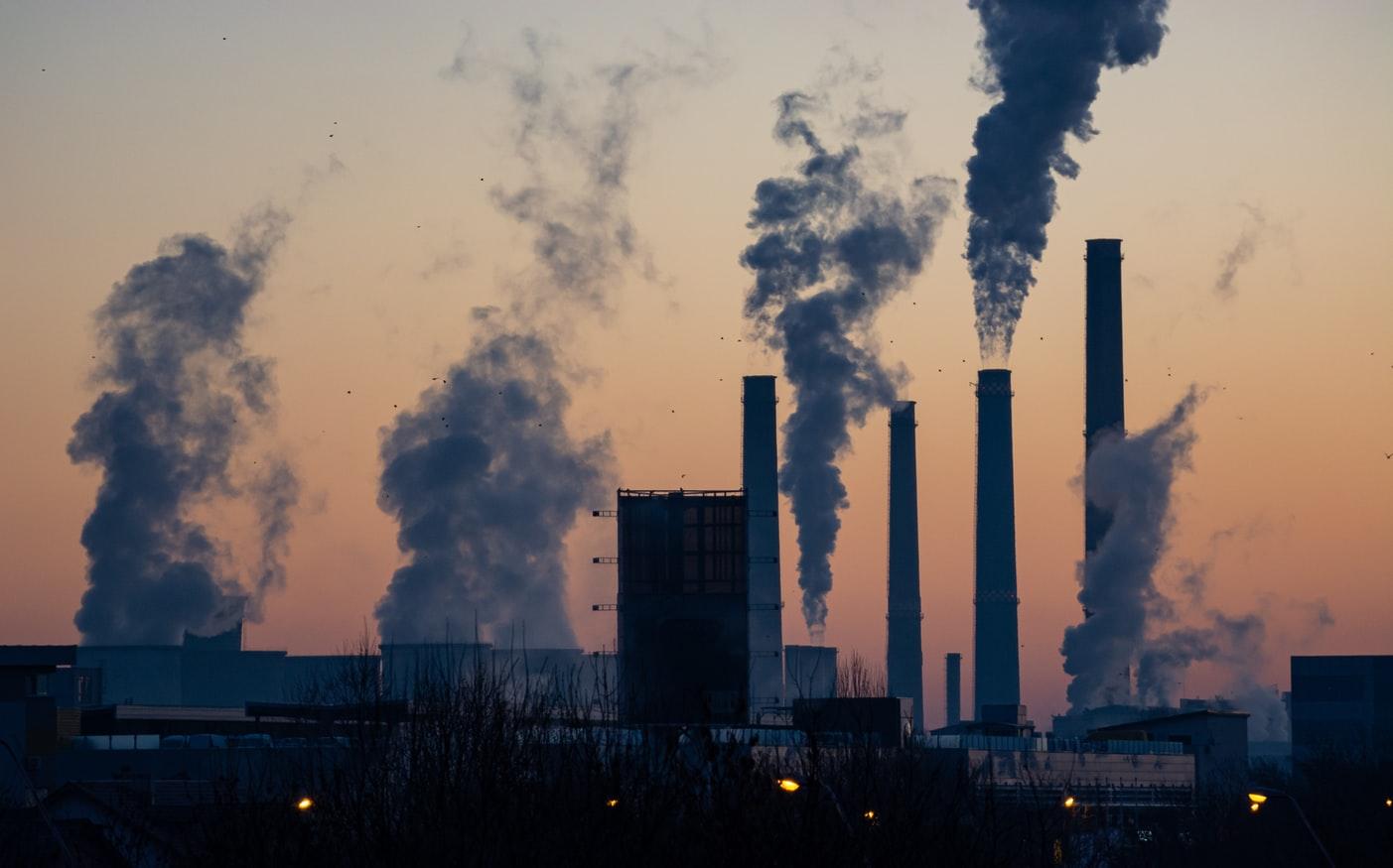 Une usine avec d'importantes colonnes de fumées vers le ciel.