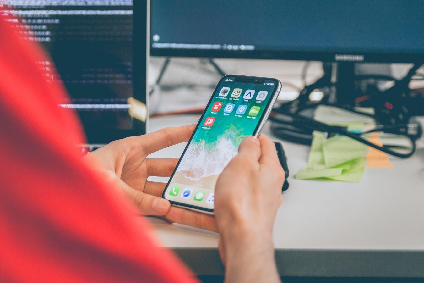 Un jeune homme manipulant un smartphone, près d'une table de travail sur laquelle repose un ordinateur.