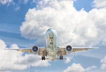 Un avion blanc et bleu dans le ciel.