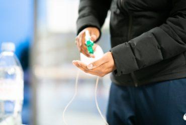 Un homme aspergeant sa main de gel hydroalcoolique