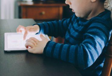 Un enfant jouant avec sa tablette, sur une table.