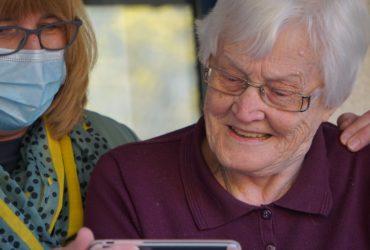 Une femme âgée manipulant un smartphone avec l'aide d'une infirmière portant un masque de protection.